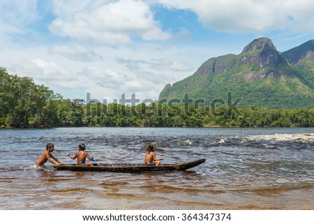 Children from the Piaroa ethnicity play on a canoe in the waters of the Autana river, in the amazonas state, in southern Venezuela