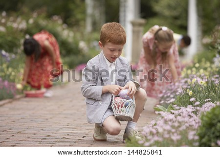 Children gathering Easter eggs in garden - stock photo