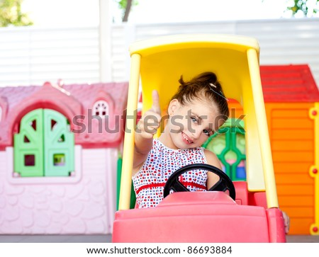 children girl driving a toy car with ok hand gesture in playground