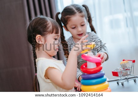 Children girls play a toy games in the room, Kids playing together with circular loop tower preschool and kindergarten education at home.