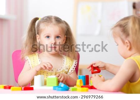 children girls play educational toys in preschool