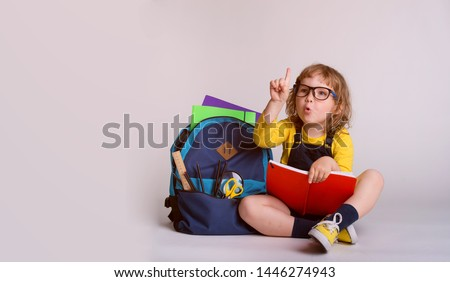 Children go back to school. Little happy  girl doing homework at home with backpack full of books, pencils. Pupil reading a book, writing and painting.  Kid is drawing. Child in glasses.