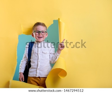 Children go back to school. Pupil of primary school with backpack and book breaking yellow paper wall. Beginning of lessons. First day of fall. Elementary student.