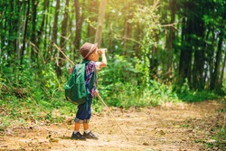 Children go hiking at backyard with backpacks at forest path. Explorer and adventure with toy binocular