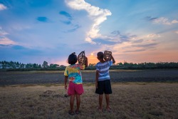 Children go out to catch fish in dry swamps. Poor Asian children who lack food, search for food in the dry land under sunset