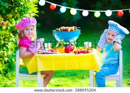 Children grilling meat. Family camping and enjoying BBQ. Brother and sister at barbecue preparing steaks and sausages. Kids eating grill and healthy vegetable meal outdoors. Garden party for child.