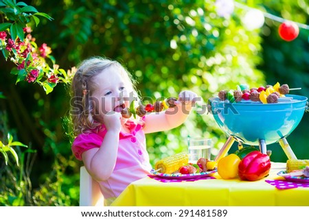 Children grilling meat. Family camping and enjoying BBQ. Little girl at barbecue preparing steaks, kebab and corn. Kids eating grill and healthy vegetable meal outdoors. Garden party for toddler child