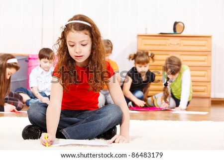 Children group drawing, a girl in red t-shirt sits in front