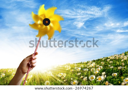 Children hand holding a yellow windmill in a flowery field in Spring - stock photo