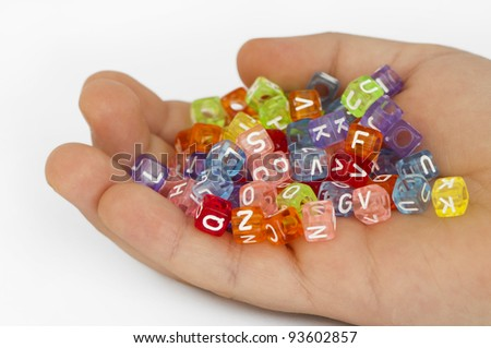Children hand holding multicolored cubes with letters