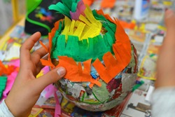 Children hands are making a pinata with colorful paper and glue.