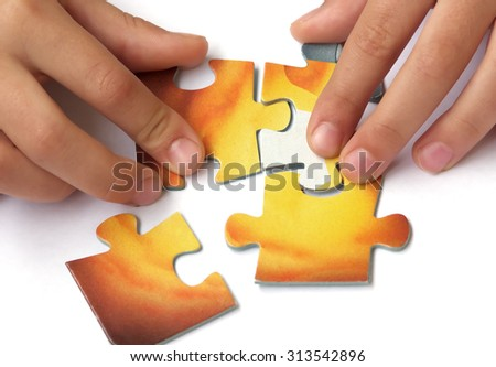 Stock Photo Children hands collect puzzle on white background.  Problem solving and teamwork concept.