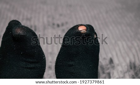 Children hands playing with his toes sticking out of socks, Old socks on boy feet, Pair of socks with hole and a finger sticking out of them, kid boy with worn out socks sitting in bed.
