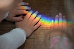 Children Hands Touching the Rainbow