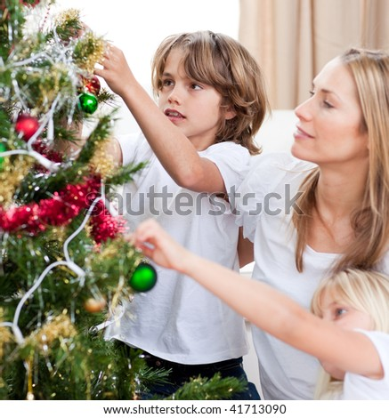 Children hanging Christmas decorations with their mother in the living-room