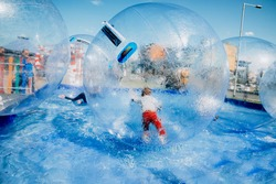 Children have fun, rolling around inside giant plastic zorbing balloons floating on water