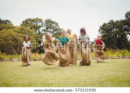 Children having a sack race in park on a sunny day #573151930