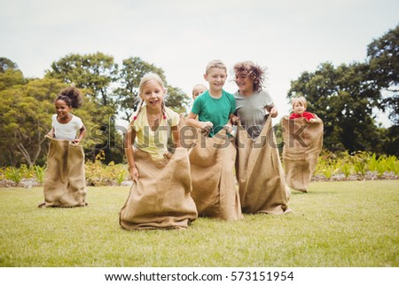 Children having a sack race in park on a sunny day #573151954