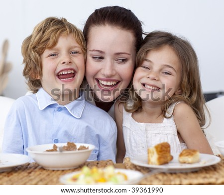 Children having breakfast in kitchen with their mother