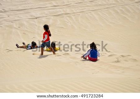 Children having fun in the desert sand #491723284
