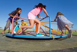 Children having fun riding a carousel in a park