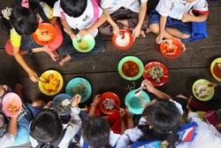 Children having lunch in asian school sitting on the floor