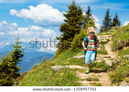 Children hiking in Alps mountains. Kids look at snow covered mountain in Austria. Spring family vacation. Little boy on hike trail in blooming alpine meadow. Outdoor fun and healthy activity. #1358997743
