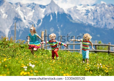 Children hiking in Alps mountains. Kids run at snow covered mountain in Austria. Spring family vacation. Little boy and girl on hike trail in blooming alpine meadow. Outdoor fun and healthy activity #1330600520
