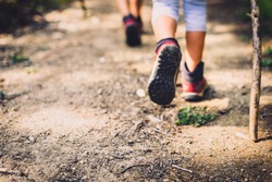 Children hiking in mountains or forest with sport hiking shoes. Girls or boys are walking trough forest path wearing mountain boots and walking sticks. Frog perspective with  blurred background.