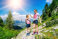 Children hiking on beautiful summer day in alps mountains Austria, resting on rock and admire amazing view to mountain peaks. Active family vacation leisure with kids.Outdoor fun and healthy activity.