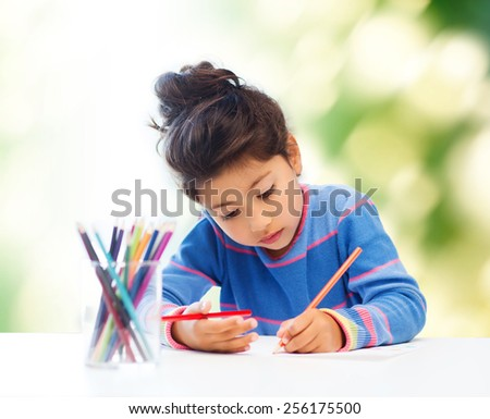 children, hobby, childhood and happy people concept - little girl drawing over green background