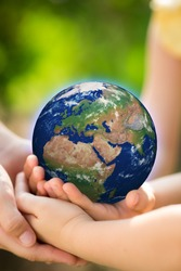 Children holding Earth in hands against green spring background. Elements of this image furnished by NASA