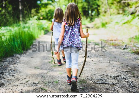 Children - identical twins girls are hiking in the mountains. Active family, parents and children mountaineering in the nature. Kids are walking in woods with walking sticks.