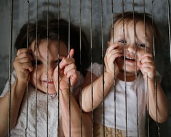 Children in a cage, the concept of restriction of freedom and violation of the rights of the child, domestic violence, quarantine and a child locked in 4 walls, childhood safety