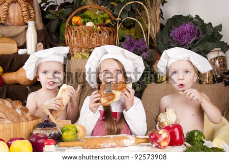 children in a chef's hats eating bread