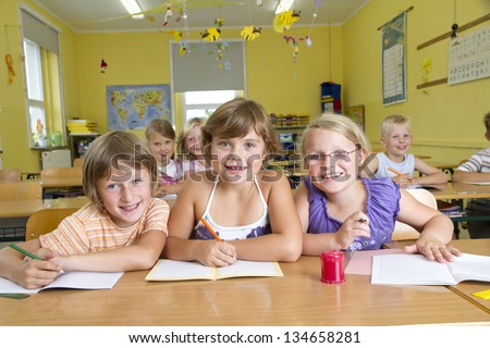 Children in a yellow classroom during a lesson. All are laughing to camera.