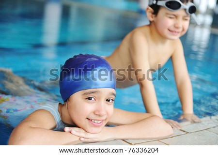 Children  in blue water of the swimming pool, summer time for fun