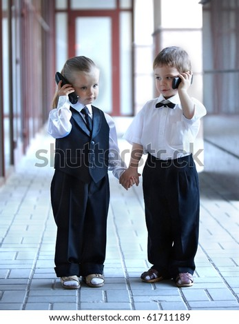 Children in business suit with mobile phone outdoors. Concept. - stock photo