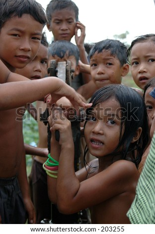 Children in Cambodia play with a water pump provided by the charity Tabitha. Taken in a village outside Phnom Penh in June 2004.