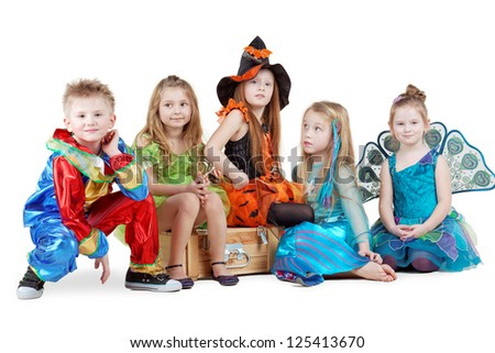 Children in carnival costumes sit on chest and on floor near it Stock photo ©