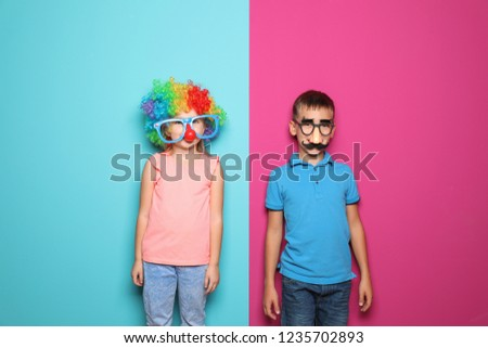 Children in funny disguise ready to celebrate April Fool's day on color background
