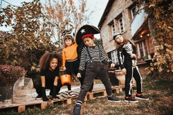 Children in Halloween costumes in front of an old house