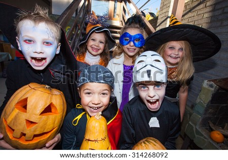 Children in halloween costumes show funny faces