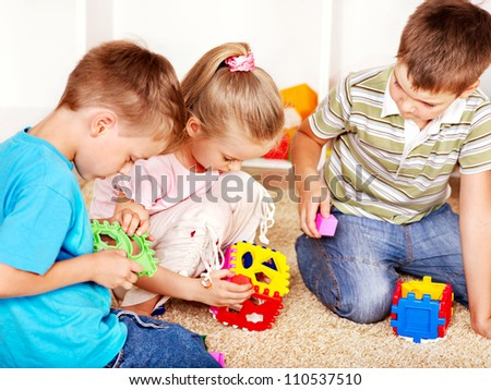 Children in kindergarten stacking block.