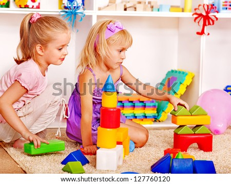 Children in kindergarten stacking block.