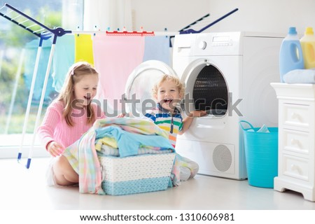 Children in laundry room with washing machine or tumble dryer. Kids help with family chores. Modern household devices and washing detergent in white sunny home. Clean washed clothes on drying rack.  #1310606981