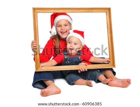 children in red christmas hats in the frame for a picture isolated on white