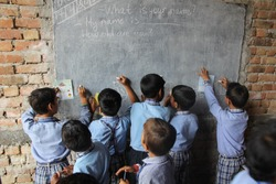 Children in rural indian village school learning to draw on the blackboard