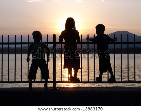 Children in silhouette on a fence by the lake