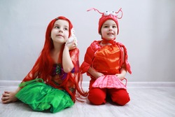 Children in smart carnival costumes on a plain background. Costume of sea fairy creatures. Mermaid and crab. Brother and sister.